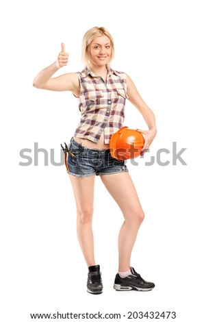 Full length portrait of a female construction worker giving a thumb up isolated on white background