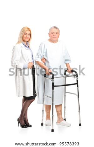Full length portrait of a female doctor or nurse helping a senior patient to use a walker isolated on white background - stock photo
