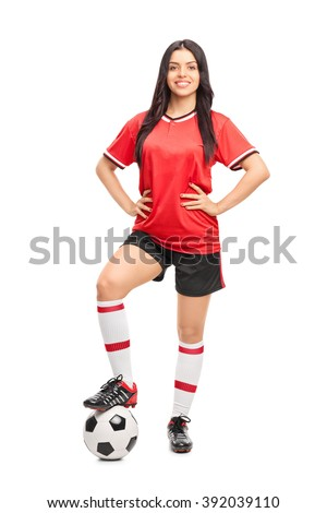 Full length portrait of a female football player in a red jersey isolated on white background - stock photo