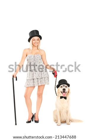 Full length portrait of a female magician holding a dog on a leash isolated on white background - stock photo