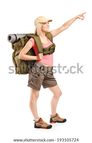 Full length portrait of a female mountaineer pointing with hand isolated on white background