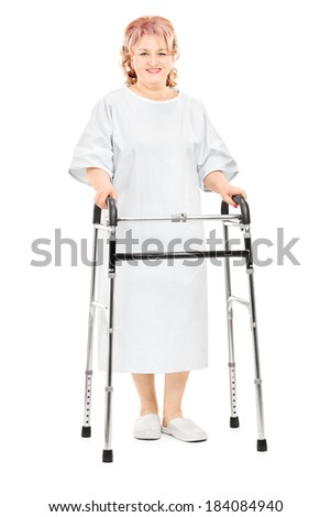 Full length portrait of a female patient walking with walker isolated on white background
