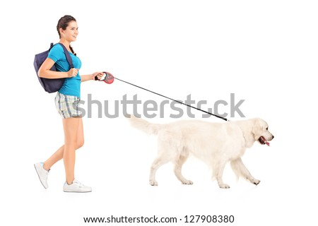 Full length portrait of a female student walking her dog isolated on white background
