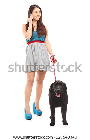 Full length portrait of a female walking her dog and talking on a mobile phone isolated on white background - stock photo