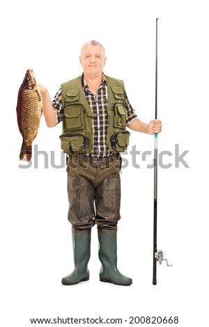 Full length portrait of a fisherman holding a fish and a fishing rod isolated on white background - stock photo