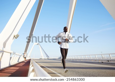 Full length portrait of a fit and athletic male running on a bridge road promenade outside - copy space area, dark skinned runner jogging against bright blue sky background  - stock photo