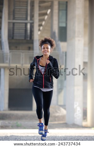 Full length portrait of a fit young woman running outdoors - stock photo