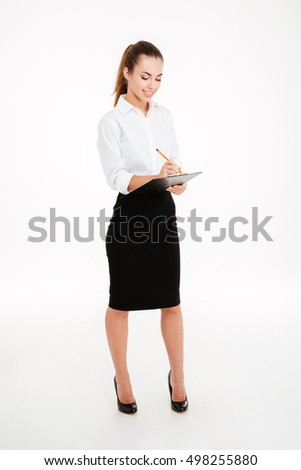 Full length portrait of a friendly young smiling businesswoman with clipboard and pen over white background