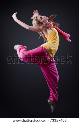 Full-length portrait of a girl dancing on a dark studio background - stock photo