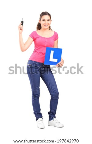 Full length portrait of a girl holding an l sign and a car key isolated on white background