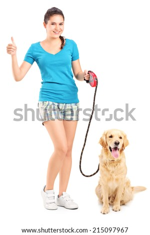 Full length portrait of a girl with a dog giving a thumb up isolated on white background