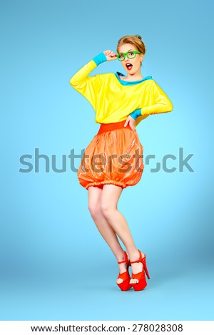 Full length portrait of a glamorous fashion model posing in vivid colourful clothes and glasses. Bright fashion. Optics, eyewear. Studio shot. - stock photo