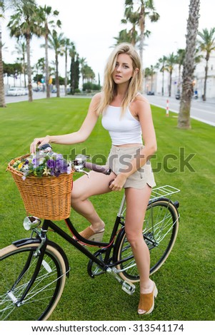 Full length portrait of a gorgeous female dressed in trendy clothes standing outdoors with her retro bicycle and looks at you, attractive blonde hair woman posing for the camera with vintage bike - stock photo
