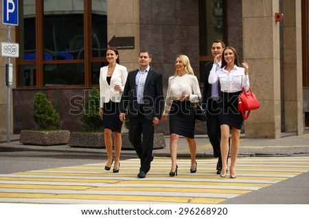 Full length portrait of a Group Of Businesspeople Crossing Summer Street
