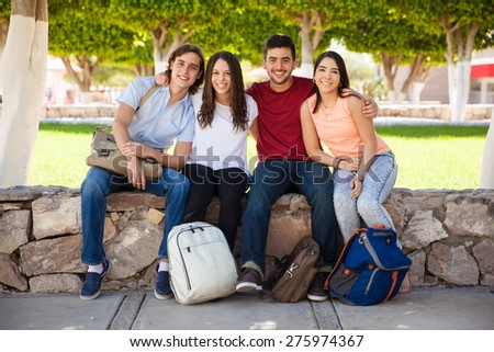 Full length portrait of a group of Hispanic college students relaxing at school