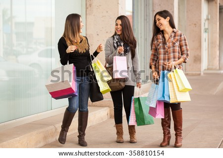 Full length portrait of a group of rich women walking around a mall with a lot of shopping bags