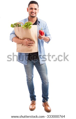 Full length portrait of a guy carrying a bag of groceries and holding a bell pepper in one hand - stock photo