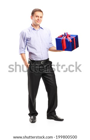 Full length portrait of a guy holding a big present isolated on white background