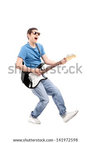 Full length portrait of a guy playing on an electric guitar isolated on white background - stock photo