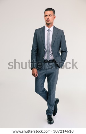 Full length portrait of a handsome businessman in suit walking on gray background - stock photo