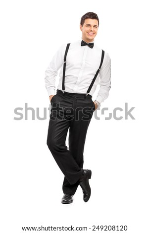 Full length portrait of a handsome guy with suspenders and bow-tie leaning against a wall isolated on white background - stock photo