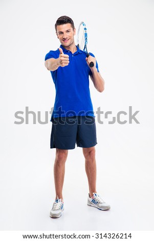Full length portrait of a handsome man holding tennis racket and showing thumb up isolated on a white background - stock photo