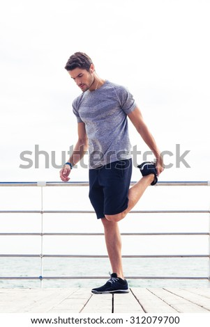 Full length portrait of a handsome man stretching legs outdoors - stock photo