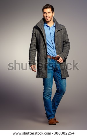 Full length portrait of a handsome man wearing jeans clothes and a coat. Men's beauty, seasonal fashion. Studio shot. - stock photo