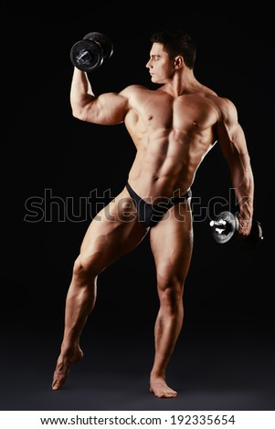Full length portrait of a handsome muscular bodybuilder posing with dumbbells over black background.