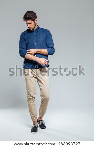 Full length portrait of a handsome serious man tacking sleeves isolated on the gray background
