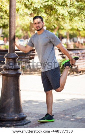 Full length portrait of a handsome young Hispanic man stretching and warming up before going for a run outdoors in a park - stock photo