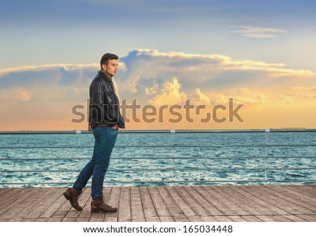 Full length portrait of a handsome young man at the quay at sunset - stock photo
