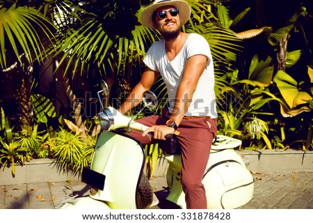Full length portrait of a handsome young man enjoy his days,ride vintage vespa on the city,Casual man posing outdoor on the street,palms background.Street style,mans fashion.hand watch,mans hat,pastel - stock photo