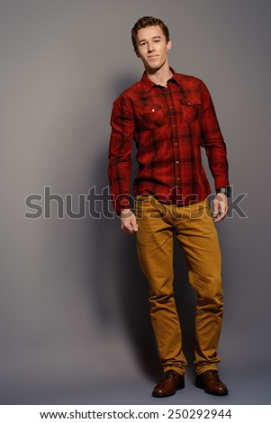 Full length portrait of a handsome young man in casual clothes. Studio shot. - stock photo