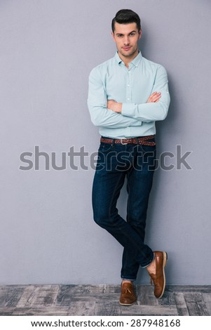 Full length portrait of a handsome young man standing with arms folded over gray background - stock photo