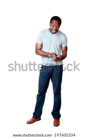 Full length portrait of a happy african man using smartphone over white background - stock photo