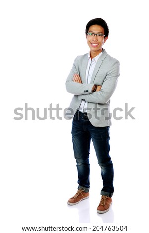 Full length portrait of a happy asian man standing with arms folded over white background - stock photo