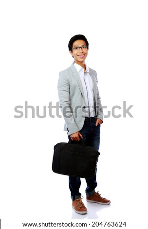 Full length portrait of a happy asian man standing with briefcase over white background - stock photo