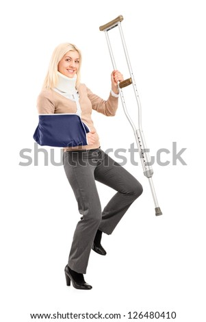 Full length portrait of a happy blond female with broken arm holding a crutch isolated on white background