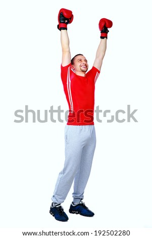 Full length portrait of a happy boxer man winner raising arms over white background