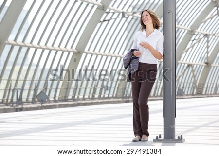 Full length portrait of a happy business woman standing at station with mobile phone - stock photo