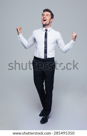Full length portrait of a happy businessman celebrating his success over gray background - stock photo