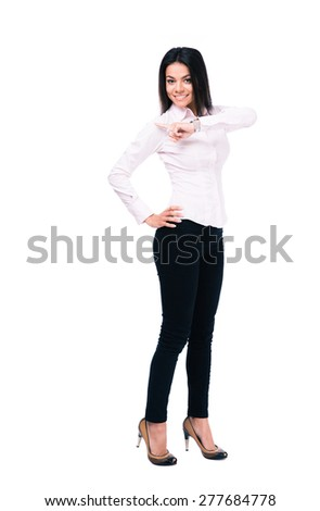 Full length portrait of a happy businesswoman pointing finger away. Isolated on a white background. Looking at camera
