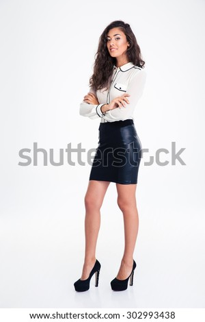 Full length portrait of a happy businesswoman standing with arms folded isolated on a white background. Looking at camera