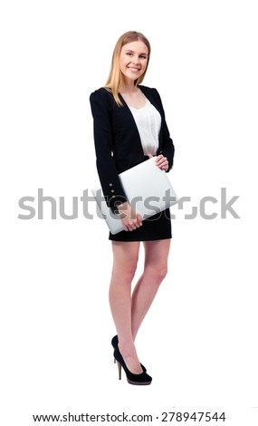 Full length portrait of a happy businesswoman standing with laptop over white background and looking at camera - stock photo