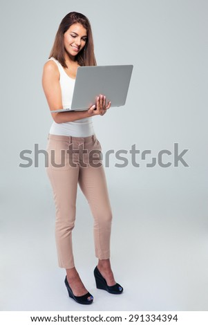 Full length portrait of a happy businesswoman using laptop over gray background - stock photo