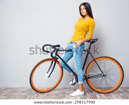 Full length portrait of a happy casual woman standing with bicycle on gray background. Looking at camera - stock photo