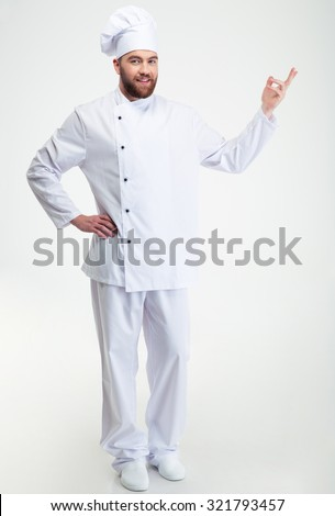Full length portrait of a happy chef cook showing welcome gesture isolated on a white background