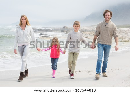 Full length portrait of a happy family of four walking hand in hand at the beach - stock photo
