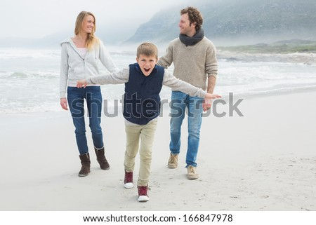 Full length portrait of a happy family of three walking at the beach - stock photo